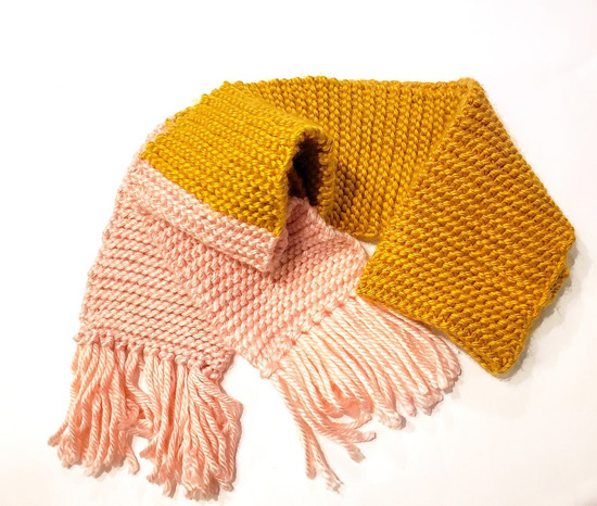 Two-tone scarf in pink and mustard yellow with fringe.