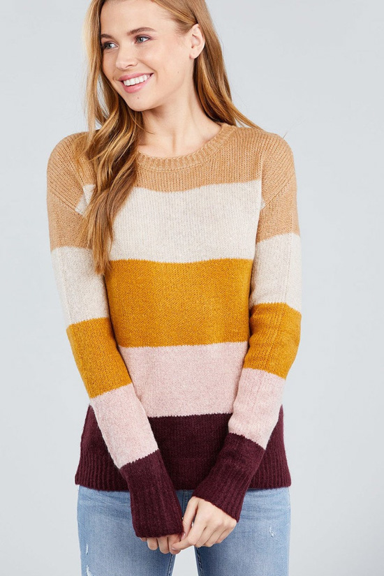 Blonde model wearing a long sleeve, color block sweater.