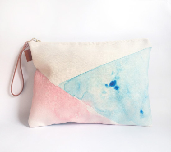 Watercolor, geometric design clutch with a brown leather wrist-strap.