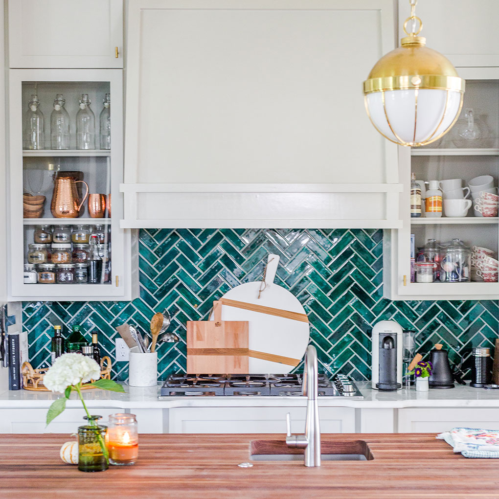 emerald green tile arranged in a herringbone pattern as a kitchen backsplash