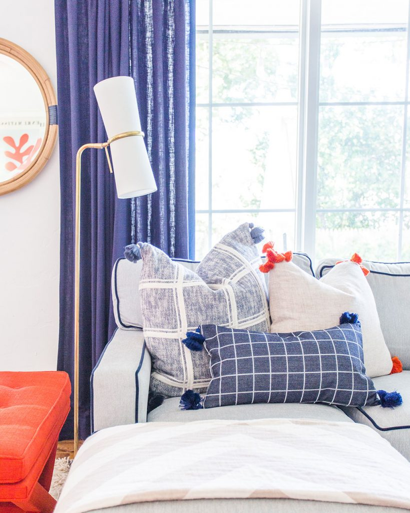 A corner of Rachel Shingleton's couch with classic blue pillows and trim in a pop of bright red-orange coral.
