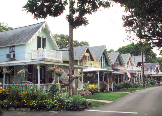 Street view of a colorful line up of cottages in a pocket neighborhood.