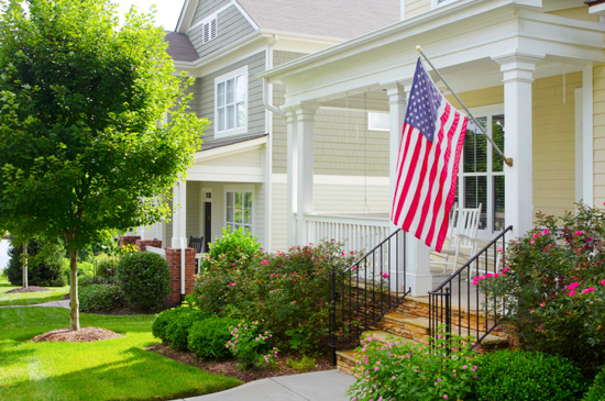 Front stoop in a pocket neighborhood with large open front porch with a prominent American flag.