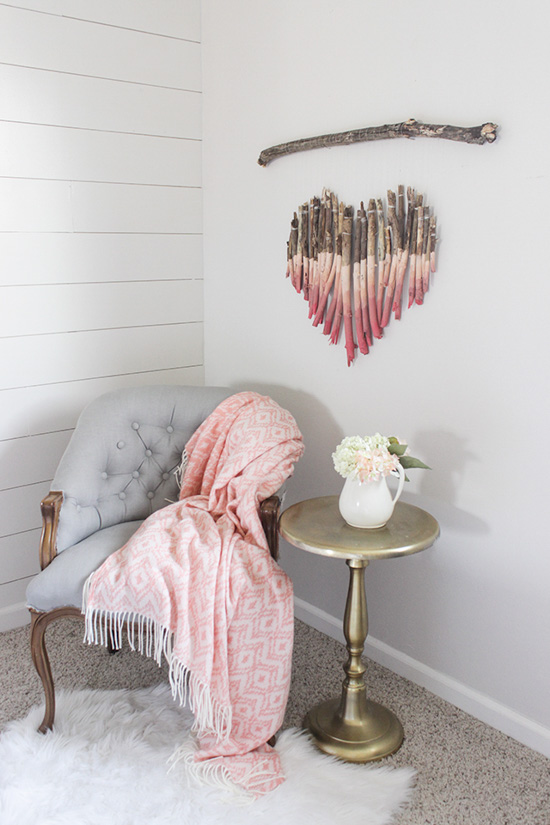 Tufted light gray chair, topped with a pink throw blanket and a handmade valentine's craft wall hanging in the shape of a heart made out of sticks.
