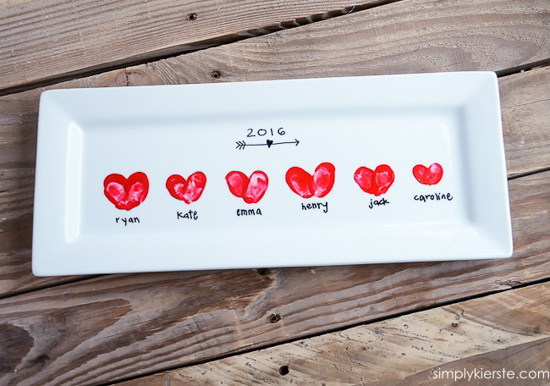 White ceramic rectangular platter Valentine's crafts with heart-shaped thumbprints, laying on a wooden table.