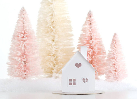 Pink and cream bottle brush trees with fake snow and a white paper crafted house with heart cutouts.