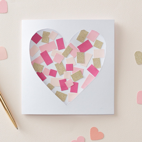 Homemade Valentine's card with a heart-shaped cutout and filled with pink and gold confetti.