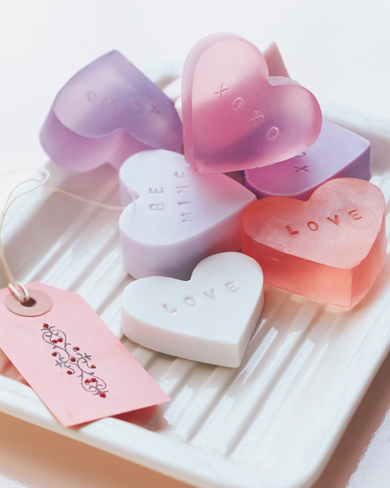 Handmade heart-shaped soaps in the shape of a heart and placed in a stack on a white glass tray.