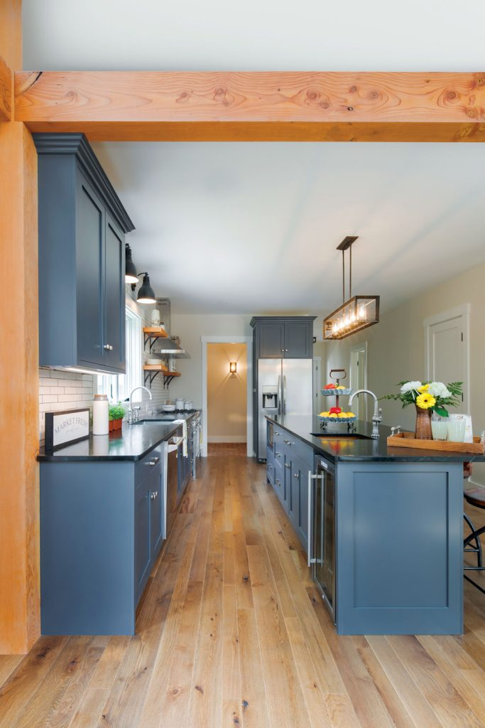 Wooden beams accent the open galley kitchen with blue shaker cabinets and stainless steal appliances.
