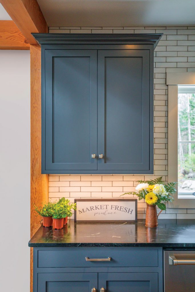Dark soapstone countertops with white subway style backsplash and fresh flowers on the counter, surrounded by blue shaker cabinets in the kitchen.