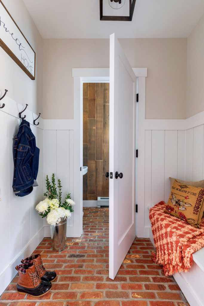 Entryway to a mudroom with white trim and red brick flooring.