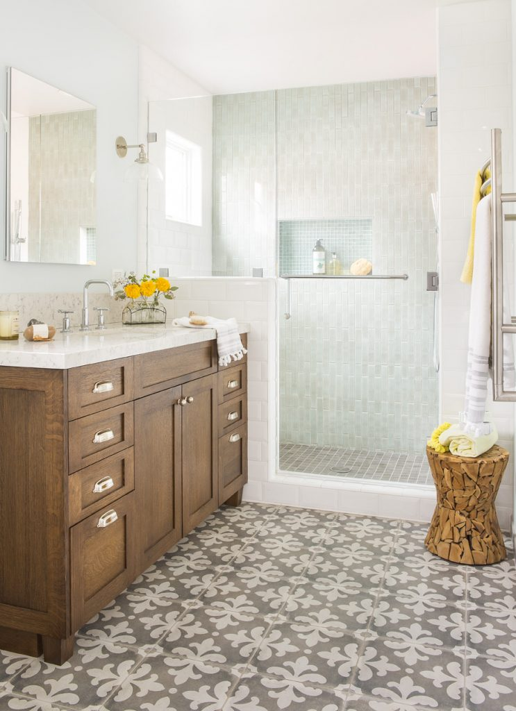 The art of the declutter. In this room master bathroom designed by Jackson Design & Remodeling, the tile choices and the beautiful design of the vanity take center stage over the small odds & ends.