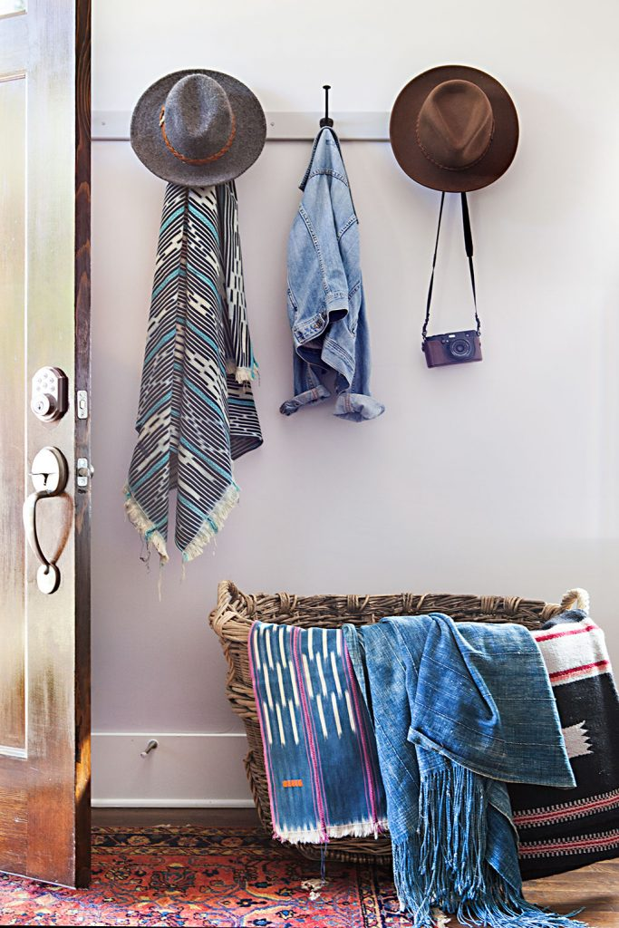 Declutter solution: stylish hooks and an oversized wide basket by the entryway of a Nashville cottage are filled with indigo textiles and stylish denim jackets, wide brimmed hats and a mexican poncho