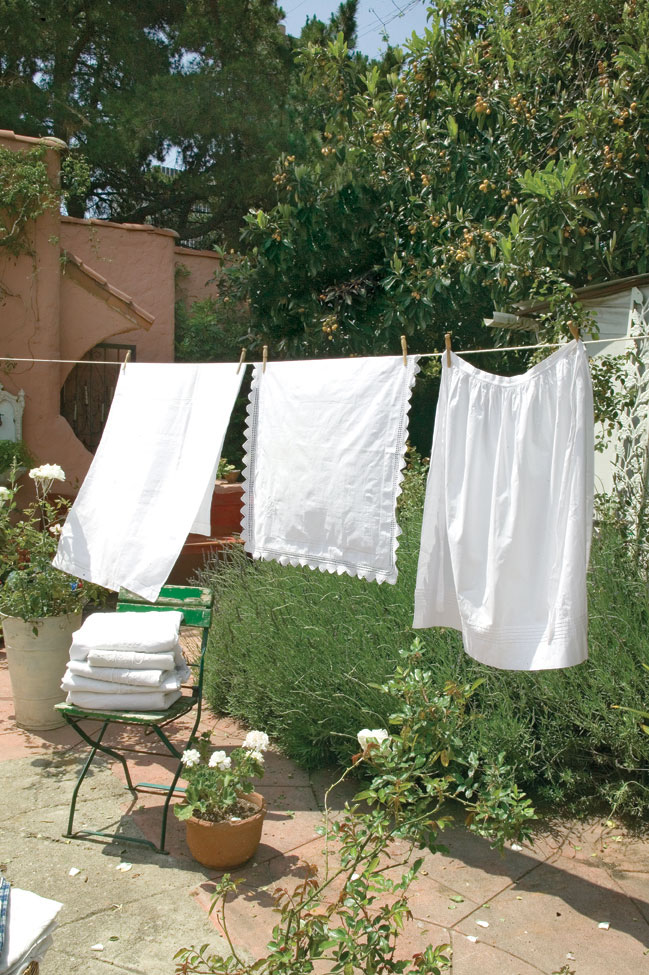 white french linens blowing in the breeze on a clothesline in the garden. Part of a home deep clean.