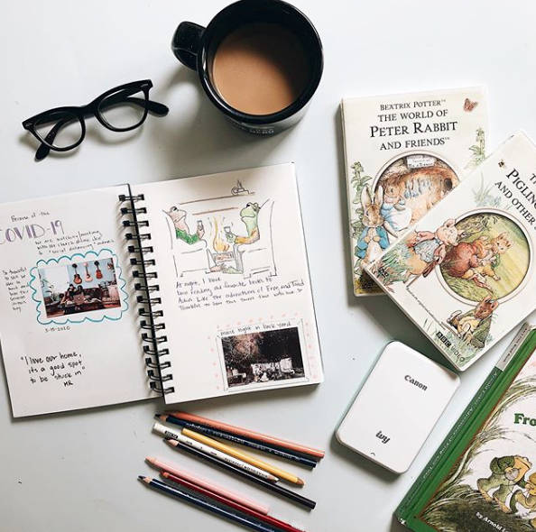 Coffee mug, reading glasses, art supplies and childrens classic books spread out on a table.