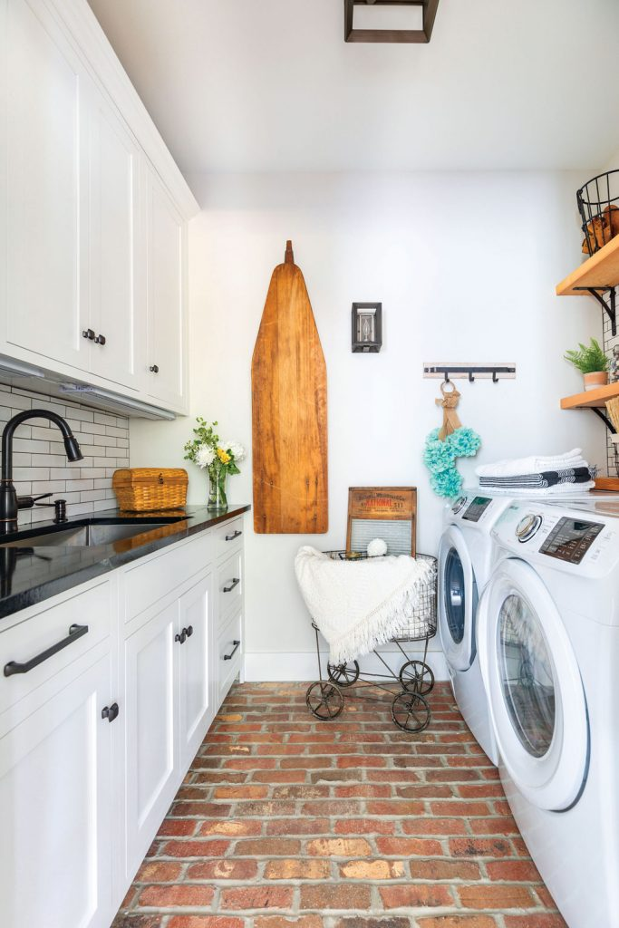Laundry room with brick flooring, white washer and dryer, open shelving and wooden ironing board.