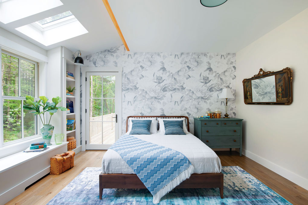 Master bedroom with cottage style blue and white accents and floral wallpapered accent wall behind the bed.
