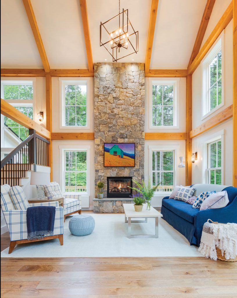Great room with a farmhouse cottage feel. Large vaulted ceiling with wooden accent beams and blue and white cozy furniture.