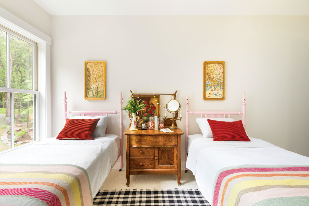 Traditional twin beds in a soft pink with striped throw blankets separated by a vintage wooden bedside table.