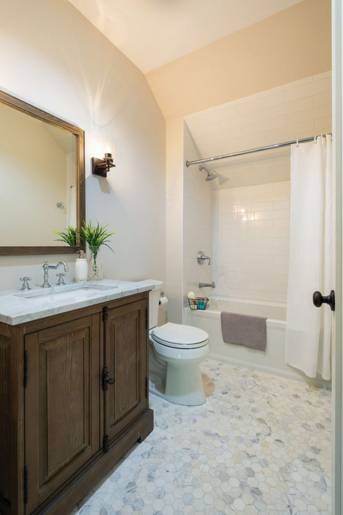 Master bathroom with custom wooden vanity and marbled, octagonal floor tiles.