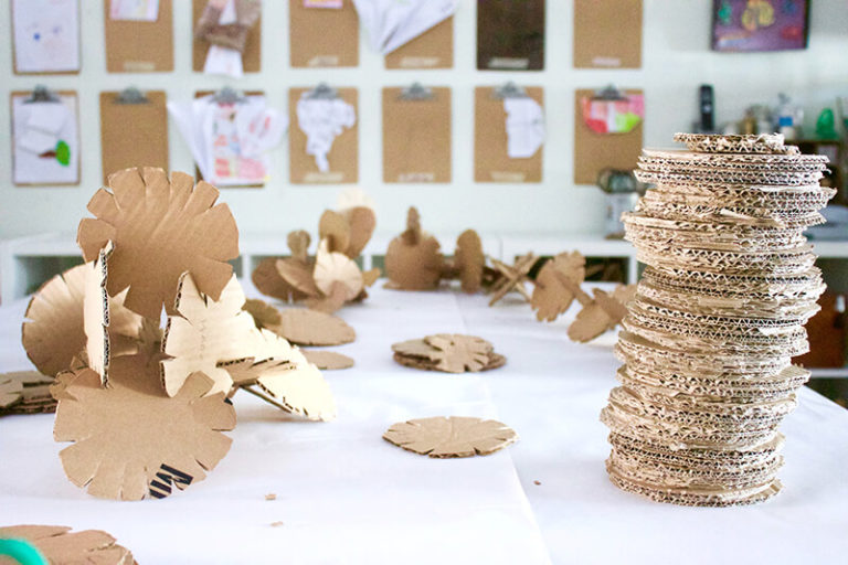 Homemade disc made of cardboard used to create sculptures placed on a table in an art room.