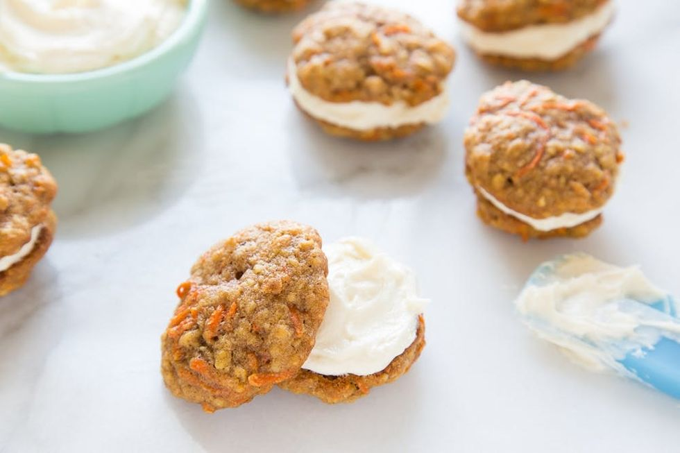 Mini carrot cake cookies sandwiched together with cream cheese frosting.