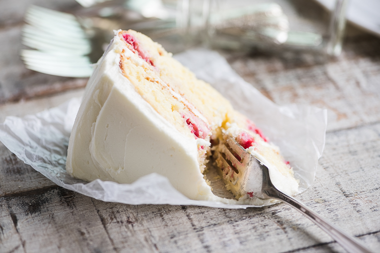 A slice of raspberry lemon cake laying on a rustic table with a ready bite on a fork.