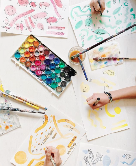 Watercolors, paintbrushes and kid hands making colorful art.