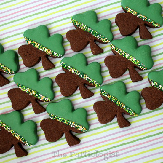 St. Patrick's Day Desserts shamrock shaped chocolate shortbread cookies half-dipped in green chocolate with a sprinkle stripe.