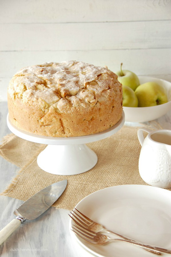 Irish apple cake displayed on a white cake stand laid on linen table cloth and bowl filled with green apples.