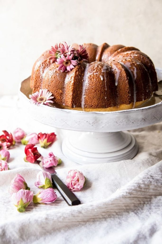 Cake stand with a brown bundt cake topped with drizzle frosting and fresh spring flowers.