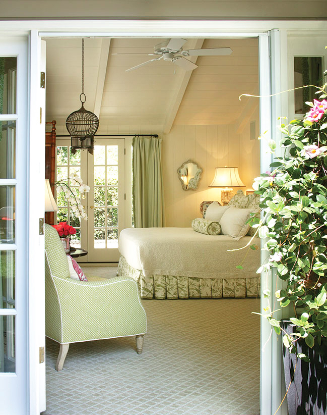 looking inside a sweet cottage bedroom through a garden door. Wisteria peeks in from the right as it frames the doorway.