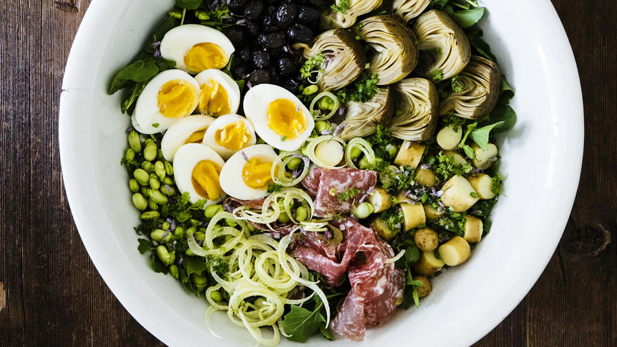 Composed mediterranean salad with eggs, artichokes, salami, potatoes and peas