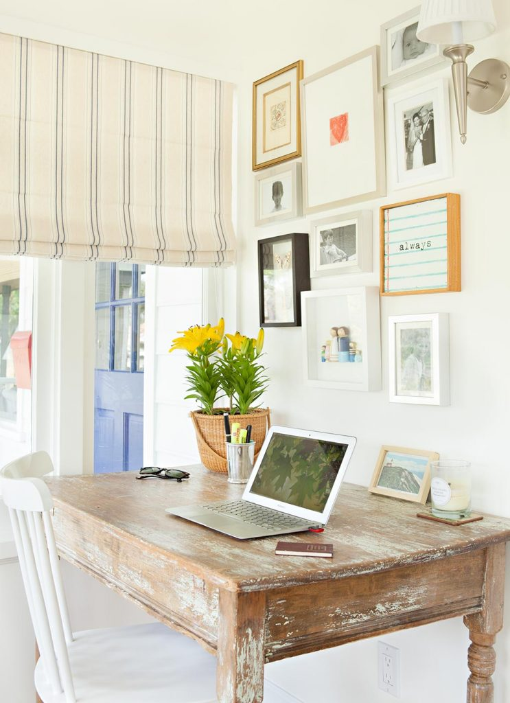 a small home office with a chippy vintage desk and charming homespun artwork on the wall