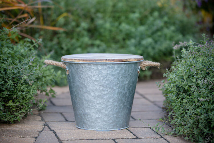 Bucket candle on patio essentials with galvanized metal
