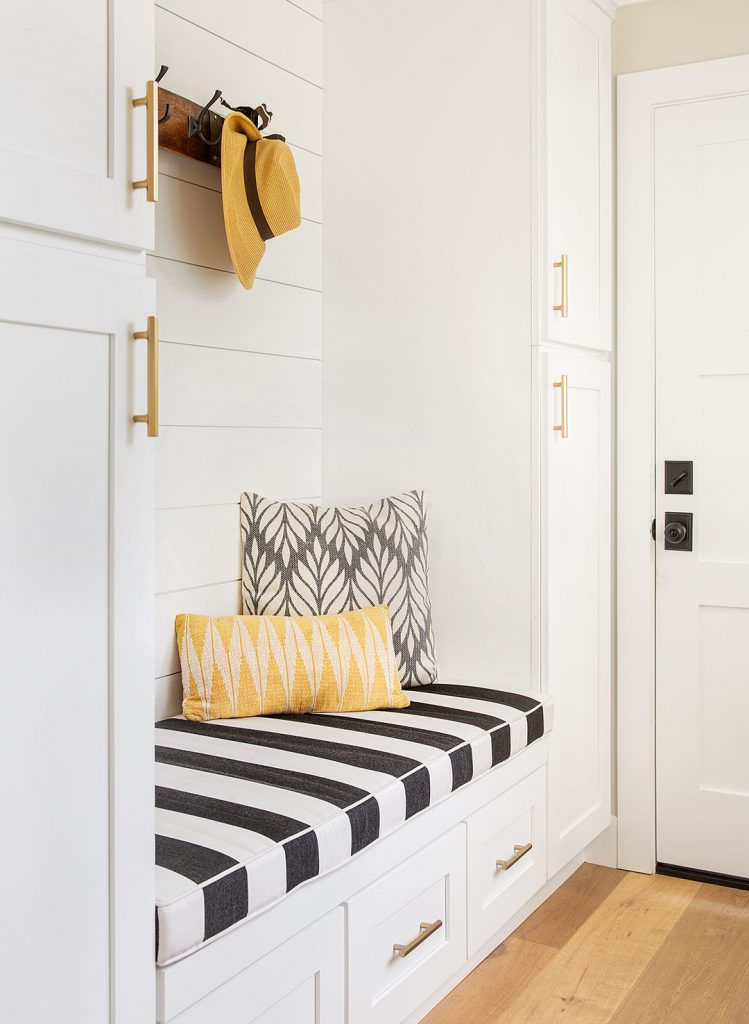 Laundry and mudroom design ideas: mudroom area with shiplap walls, a striped built in bench cushion and modern floral pillows