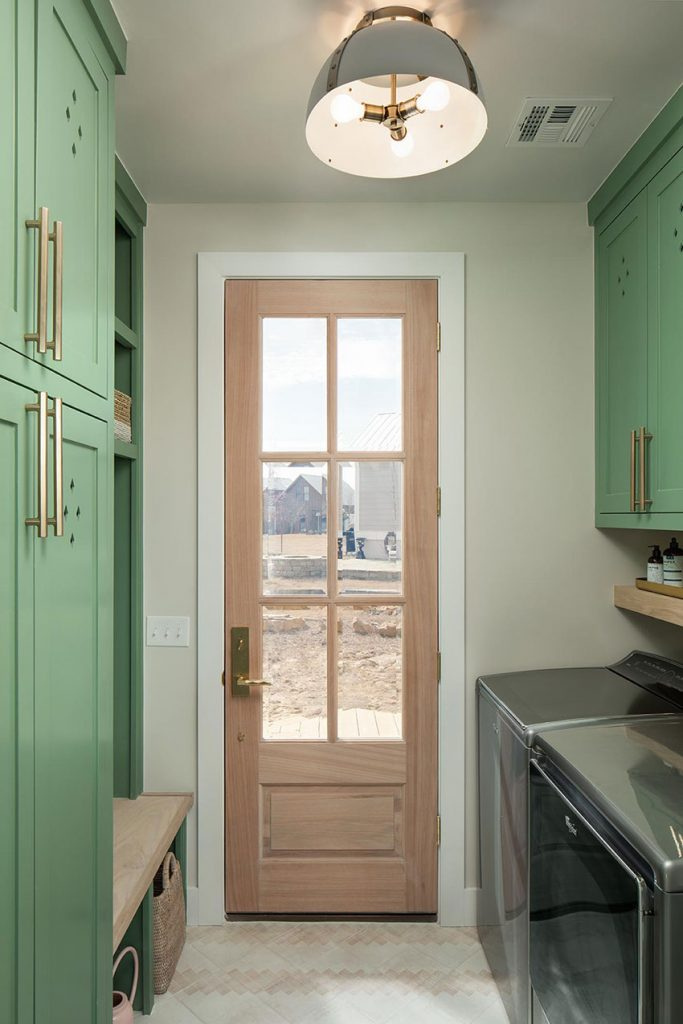 laundry and mudroom design by Rachel Shingleton. Soft green cabinets are complimented by brass hardware