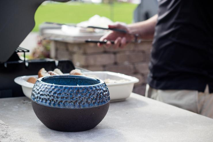 Blue ceramic pot with candle inside on tabletop