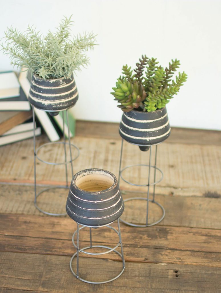 Industrialized Modern Black_Clay_Planters_With_Metal_Stands planted with succulents on a worn wooden tabletop