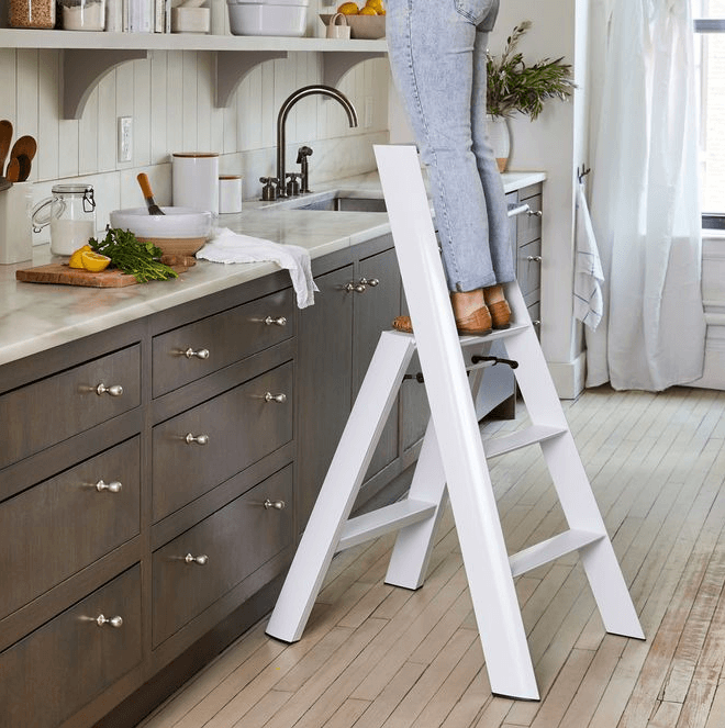 Woman standing on step ladder in kitchen