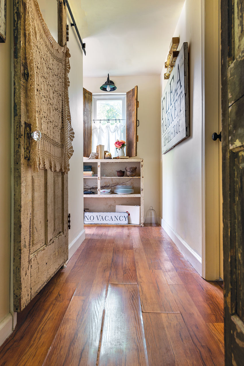 These interior of a cozy country cottage shutters that Mickie's husband built from salvaged wood are a fun twist on the traditionally exterior window