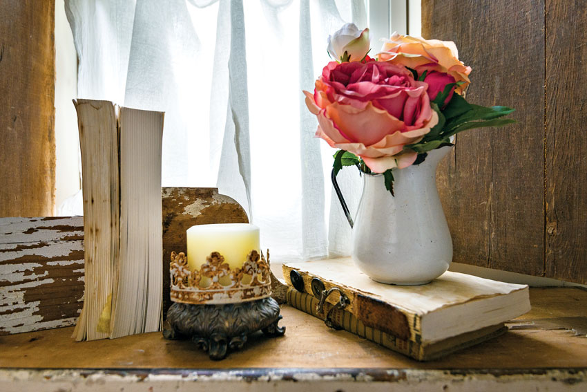 Table vignetter with old books, coral roses in white vase with a candle [A cozy country cottage]
