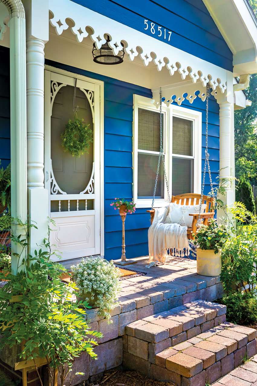 Porch swing on small front porch of blue and white country cottage