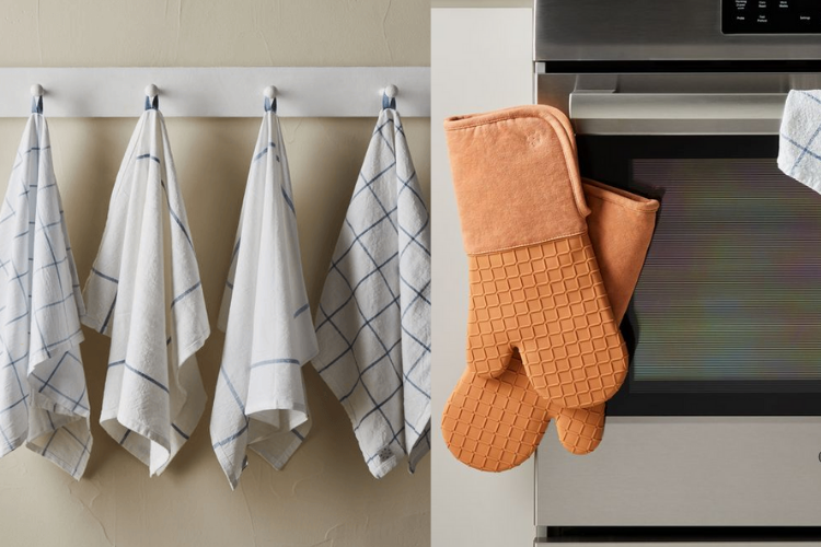 tea towels hanging on a rack and orange oven mitts hanging on an oven