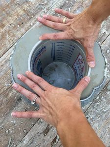 Bucket is pressed into the cement pumpkin filling to create a hollow middle where flowers can be put once dry.