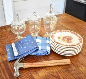 Hammer, plates, apothecary jars, and towels on a wood surface