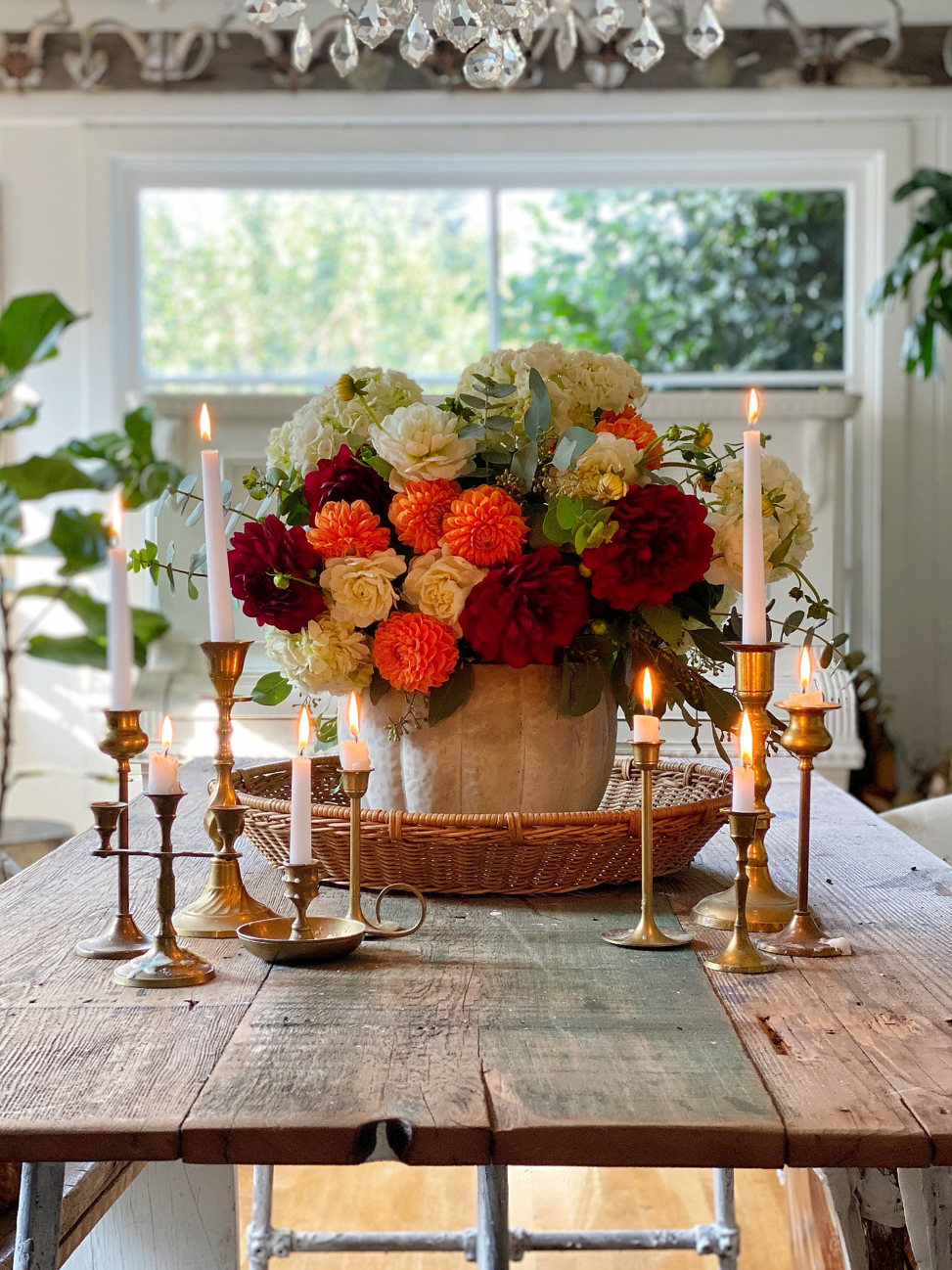 Cement pumpkin bowl sits on a wood table, filled with flowers and surrounded by vintage candles.
