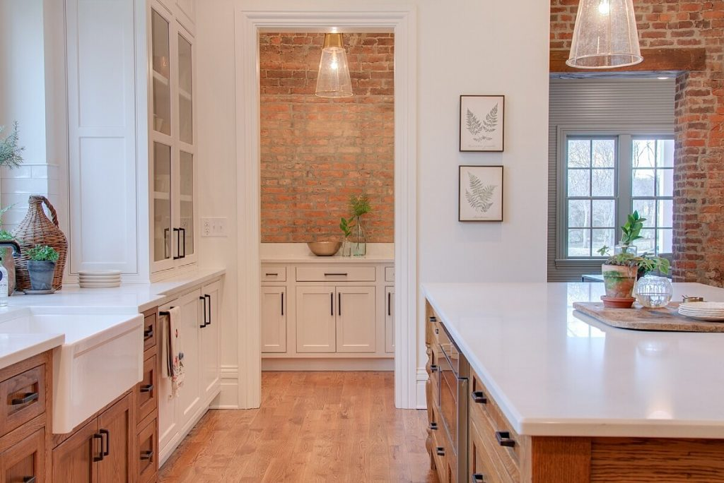Kitchen with reclaimed brick accent walls, white countertops and wood floors