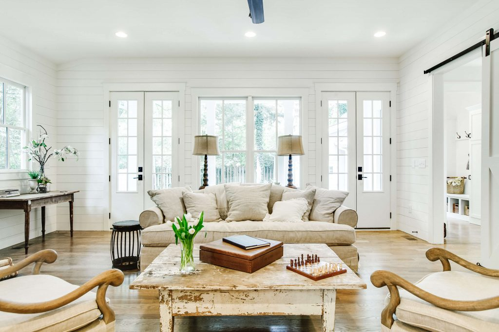 Living room with white shiplap walls, a vintage coffee table and neutral furniture.