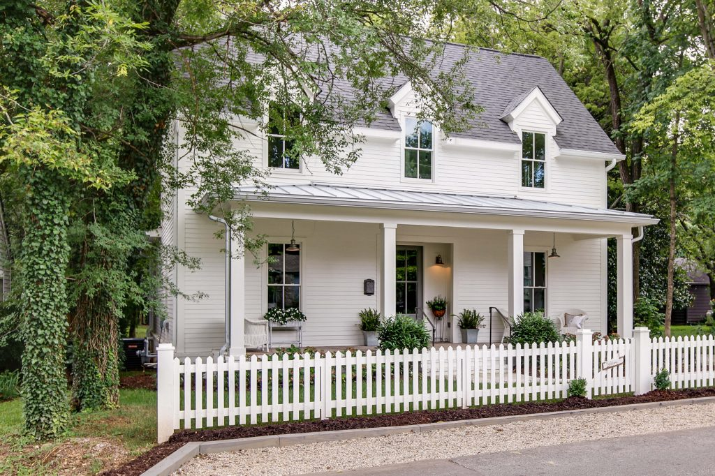 White cottage-style home exterior with white picket fence